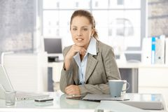 Young businesswoman sitting in bright office Royalty Free Stock Image