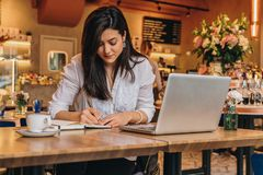 Businesswoman is sitting in cafe at table in front of laptop, making notes in notebook, working.Student learning online. Young businesswoman is sitting in cafe Stock Photo