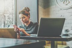 Young businesswoman sitting in cafe at table near window and using smartphone. On desk is laptop and cup of coffee. Royalty Free Stock Images