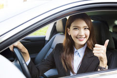 Young businesswoman sitting in car and showing thumbs up Stock Photo
