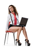 Young businesswoman sitting on chair with laptop Stock Photo