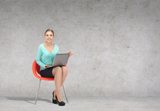 Young businesswoman sitting in chair with laptop Stock Images