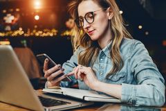 Young businesswoman is sitting in coffee shop at table in front of computer and notebook,using smartphone. Social media. stock photos