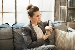 Young businesswoman is sitting on couch with cup of coffee Royalty Free Stock Images