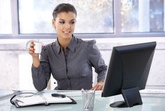 Young businesswoman sitting at desk Stock Images