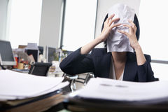 Young businesswoman sitting at desk covering her face with a paper Stock Photography