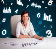 Young businesswoman sitting at desk with diagrams and statistics Stock Images