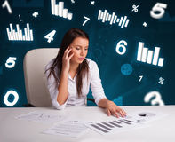 Young businesswoman sitting at desk with diagrams and statistics. Pretty young businesswoman sitting at desk with diagrams and statistics Royalty Free Stock Image