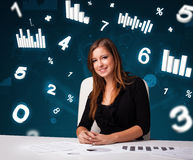 Young businesswoman sitting at desk with diagrams and statistics Stock Image