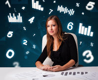 Young businesswoman sitting at desk with diagrams and statistics Stock Photo