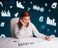 Young businesswoman sitting at desk with diagrams and statistics Royalty Free Stock Photos
