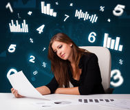 Young businesswoman sitting at desk with diagrams and statistics Royalty Free Stock Photo