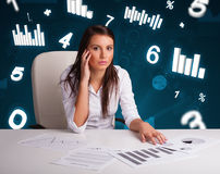 Young businesswoman sitting at desk with diagrams and statistics Royalty Free Stock Images