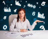 Young businesswoman sitting at desk with diagrams and statistics stock photos