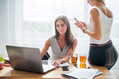 Young businesswoman sitting at desk front laptop computer with her coleague. Coffee break office Royalty Free Stock Images