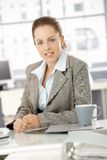 Young businesswoman sitting by desk in office Royalty Free Stock Images