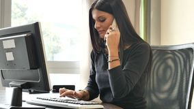 Young businesswoman sitting at desk in office busy on phone stock video footage