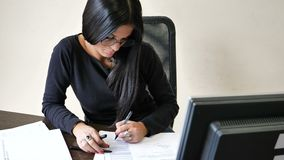 Young businesswoman sitting at desk in office busy on phone. Serious attractive young businesswoman sitting at desk in office busy talking on phone stock footage