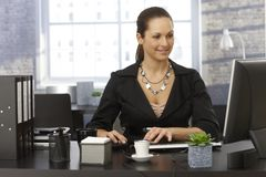 Young businesswoman sitting at desk Stock Image