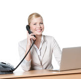 Young businesswoman sitting at a desk and talking by phone Royalty Free Stock Photography