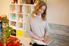 Young businesswoman sitting at desk and working. Beautiful woman fills planner Stock Photo