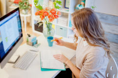 Young businesswoman sitting at desk and working. Beautiful woman and her workplace Stock Photography