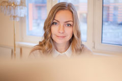 Young businesswoman sitting at desk and working. Beautiful woman and her workplace Royalty Free Stock Photos