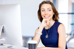 Young businesswoman sitting at desk and working Stock Images