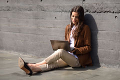 Young businesswoman sitting on floor looking at her laptop compu Royalty Free Stock Photography