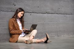 Young businesswoman sitting on floor looking at her laptop compu Royalty Free Stock Photo
