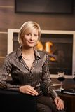 Young businesswoman sitting in front of fireplace Stock Photos