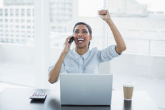 Young businesswoman sitting at her desk cheering Stock Image