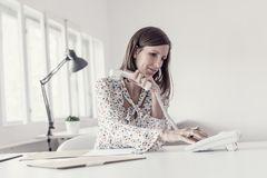 Young businesswoman sitting at her office desk making a telephone call using white phone royalty free stock photo