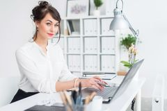Young businesswoman sitting at her workplace, working out new business ideas, wearing formal suit and glasses, looking. Aside Royalty Free Stock Photo
