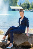 Young Businesswoman Sitting on Large Rock by Lake Stock Photo
