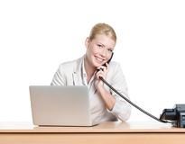Young businesswoman sitting at a office table and talking by phone Stock Photography