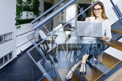 Young businesswoman sitting oh the office stairs and having coff Stock Photography