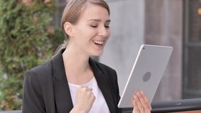 Young Businesswoman  Sitting Outdoor and Cheering Success on Tablet. 4k high quality, 4k high quality stock video