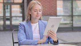 Young businesswoman sitting outdoor and using tablet stock video