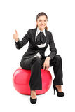 Young businesswoman sitting on pilates ball and giving thumb up Stock Image