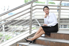 Young businesswoman sitting at stairway and her computer with sm Stock Photography