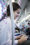 Young businesswoman sitting on the subway and using her phone Royalty Free Stock Photography