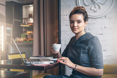 Young businesswoman sitting at table in cafe, drinking coffee and looking at camera. Stock Image