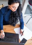 Young businesswoman sitting at table in cafe in front of laptop with inscription on screen e-learning and image of. Square academic cap and making notes in stock photography