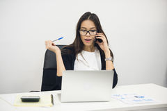 Young businesswoman sitting and talking on phone Stock Photo