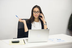 Young businesswoman sitting and talking on phone Royalty Free Stock Photography