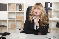 Young businesswoman sitting thinking. At her desk as she stares into the distance in deep thought as she tries to come up with a business strategy or solution Stock Image