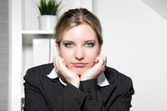 Young businesswoman sitting thinking Stock Images