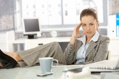 Young businesswoman sitting tired in office Stock Image