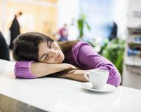Young businesswoman sleeping at desk in office Stock Image